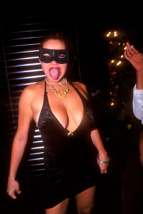 Masked woman at the door of a Miami Beach nightclub on Washington Avenue sticks out her tongue.