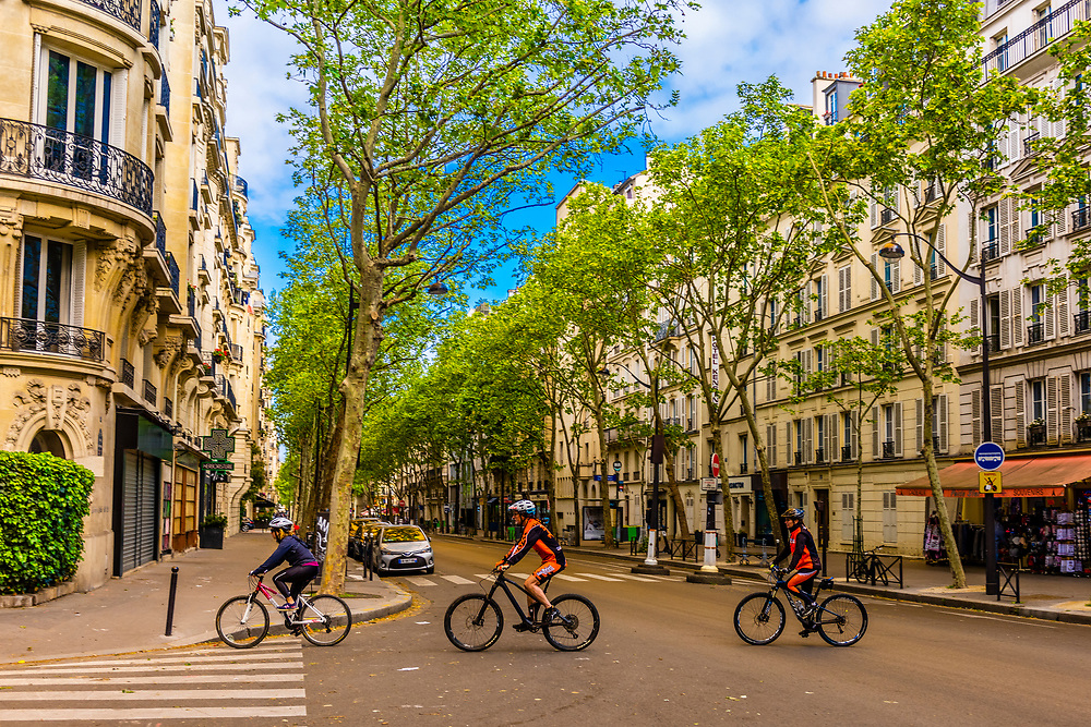 A family riding their bicycles toward Champ de Mars Park and the Eiffel Tower, Paris, France.