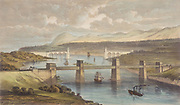 Britannia Tubular Bridge over Menai Straits between Welsh mainland and Angelsea. Chester and Holyhead Railway. Begun 1846, opened 18 March 1850. Engineer Robert Stephenson. Box girder bridge. In the background is Thomas Telford's road suspension bridge built 1820-1826.
