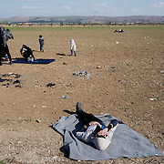 Afghans rest in the field behind the petrol station near Idomani. The kids enjoy the warmth of the sun and playing. In the last few months the fields near this petrol station have become a transit camp for thousands of refugees and migrants waiting to cross to Greek Macedonian border.