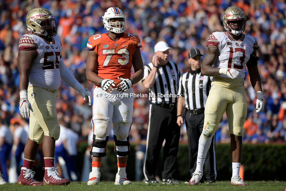 Florida offensive lineman Martez Ivey (73) lines up for a play at the line of scrimmage with Florida State defensive tackle Fredrick Jones (55) and defensive end Joshua Kaindoh (13) during the second half of an NCAA college football game Saturday, Nov. 25, 2017, in Gainesville, Fla. FSU won 38-22. (Photo by Phelan M. Ebenhack)