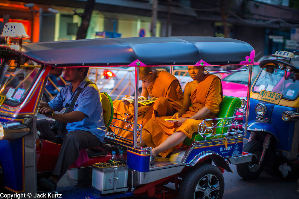 07 DECEMBER 2012 - BANGKOK, THAILAND:  Buddhist monks in a tuk-tuk (three wheeled taxi) in traffic in the Chinatown section of Bangkok, Thailand. Chinatown is the entrepreneurial hub of Bangkok, with thousands of family owned businesses selling wholesale merchandise in everything from food like rice, peanuts and meats, to dry goods like toys and shoes. Tuk-tuks are three wheeled taxis that use a motorcycle engine. In one form or another they are common in much of Asia.     PHOTO BY JACK KURTZ