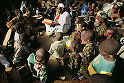 """The Imam of Kouakourou village in Mali teaches a Koranic lesson to students. Several of Soumana Natomo's children attend these classes, along with classes at what they call, """"the modern school"""" taught in French, where they learn math and reading. The Natomo family lives in two mud brick houses in the village of Kouakourou, Mali, on the banks of the Niger River. Material World Project."""