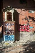 A street shrine and graffiti in a back street of mediaeval Genoa, Italy.