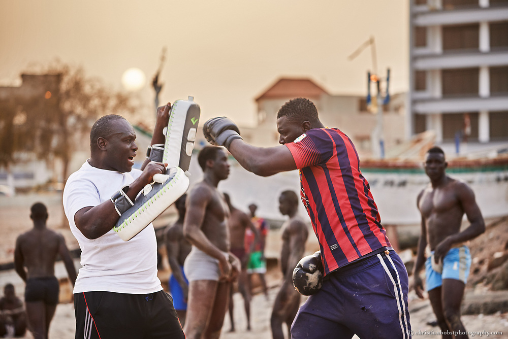 """Wrestlers practice """"la lutte avec frappe"""" (a form of Senegalese wrestling which allows boxing) during the evening hours at the wrestling school of ex-wrestler Boy Kaire on the beach of Dakar's Corniche on March 31, 2015."""