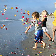 Kieran throws petals on shore during the paddle-out in memory of his sister Molly Rowlee, at Wrightsville Beach, NC. The event also helped support the Molly Fund  a non-profit dedicated to helping children with lymphoma and their families.