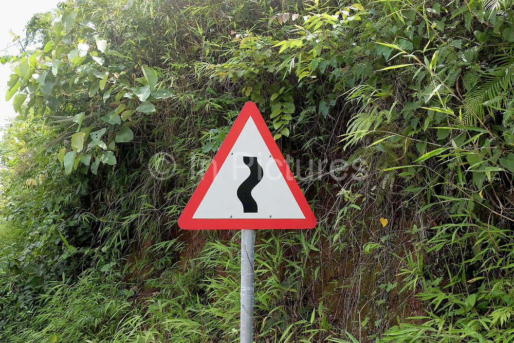 A road sign depicting a winding road in a mountainous region of Phongsaly province, Lao PDR.