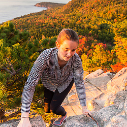 """A woman hiking """"The Beehive"""" in fall in Maine's Acadia National Park."""