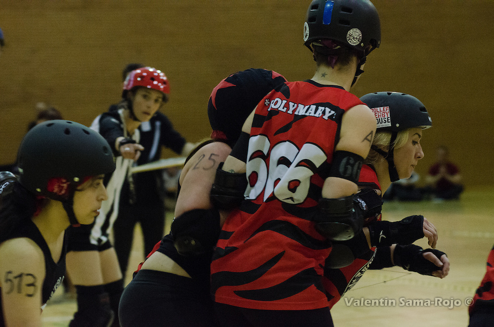 Jammer of Freaky Mons'ter Derby Ladies, 25 Owl Blacks, being blocked by two players of Roller Derby Madrid during the game held in Madrid.