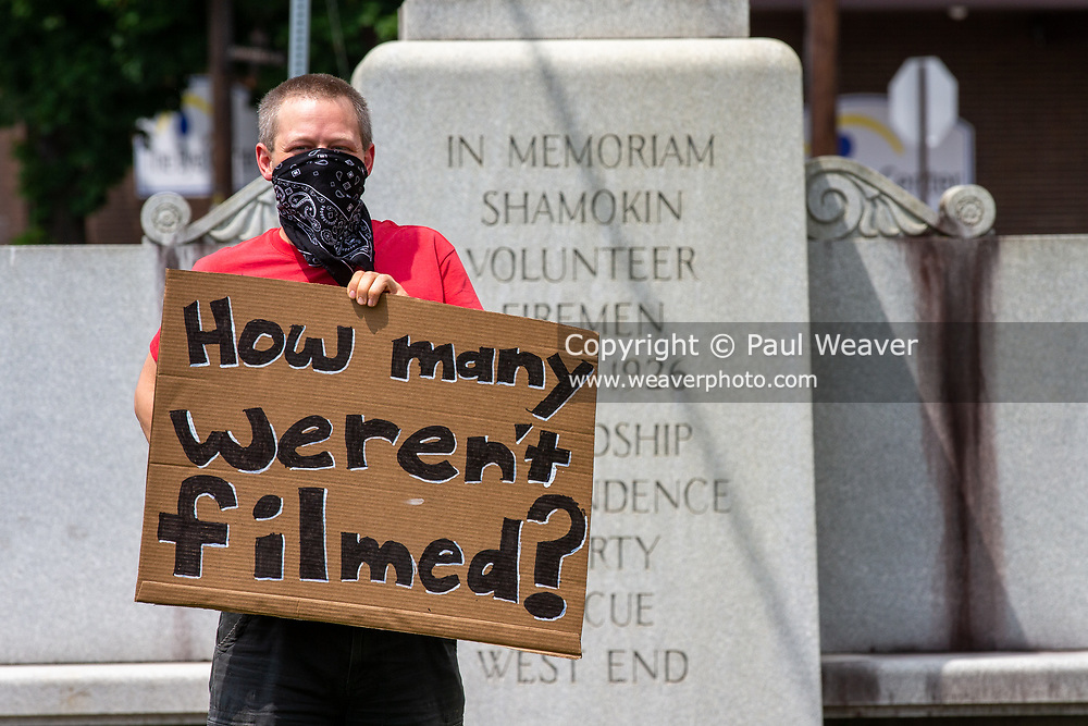 """Shamokin, PA (June 4, 2020) -- A protester holds a sign reading """"how many weren't filmed?"""" at a Black Lives Matter protest in Shamokin. About 30 people gathered at Market and Independence Streets to protest police violence and racism."""