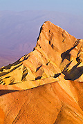Dawn light on Manly Beacon from Zabriskie Point, Death Valley National Park. California