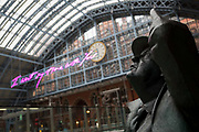 The statue of poet John Betjeman by Martin Jennings looks up to the new artwork entitled I Want My Time With You by British Britpop artist Tracy Emin which hangs over the main concourse at St. Pancras Station, on 10th April 2018, in London, England. In the sixth year of the Terrace Wires Commission - and in celebration of the 150th anniversary of St Pancras International and the 250th anniversary of the Royal Academy of Arts, at one of Londons mainline station, the London hub for Eurostar - the 20 metre-long greeting to commuters reads I Want My Time With You and Emin thinks that arriving by train and being met by a lover as they put their arms around them, is very romantic. The Brexit-opposing artist also said she wanted to make a statement that reaches out to everybody from Europe arriving in to London.