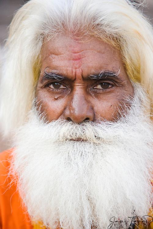 Man with bush white hair and beard wearing an orange tunic stares into the camera at the Dasaswamedh ghat in Varanasi, Uttar Pradesh, India