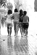 MONOCHROME<br /> Young Balinese girls caught in torrential downpour huddle together.<br /> Sanur, Bali, Indonesia