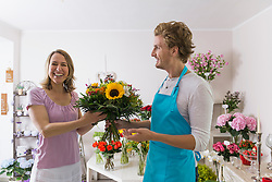 Salesman with customer in flower shop, smiling