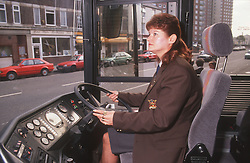 Female bus driver at work driving bus,