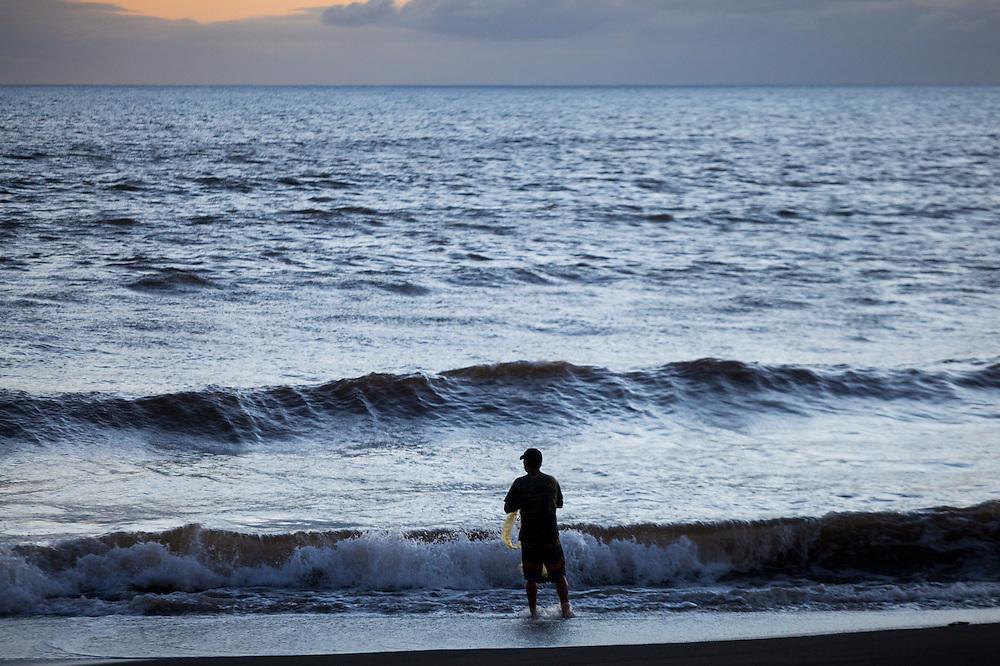 A man holds a fishing net as he steps out into the ocean on the beach at Waimea, Kauai, Hawaii.