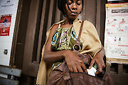 Marielle Gnabrayou Digbeto, 28, puts a pill bottle into her purse as she leaves the pharmacy at the Koumassi general hospital in Abidjan Cote d'Ivoire on Friday July 19, 2013. Marielle is pregnant with her first child and HIV positive. She's taking drugs for eMTCT, but doesn't want people to know for fear of being rejected. She lives across town but comes to the Koumassi hospital so that nobody will find out.
