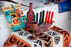 Traditional symbols of Kwanzaa.  Kikombe cha Umoja (The Unity Cup), Kinara (The Candle Holder), Mishumaa Saba (The Seven Candles), Mazao (The Crops), Mkeka (The Mat), and Zawadi(The Gifts)