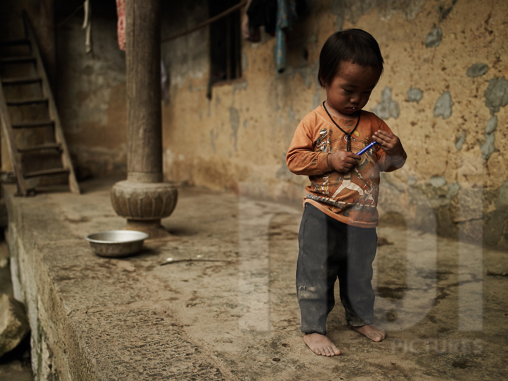 A young dirty ethnic boy holds a pen in his hands. Ha Giang province, Vietnam, Asia