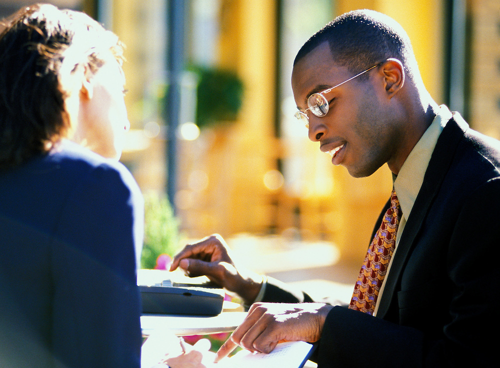 A man and woman meet at an outdoor cafe over business.