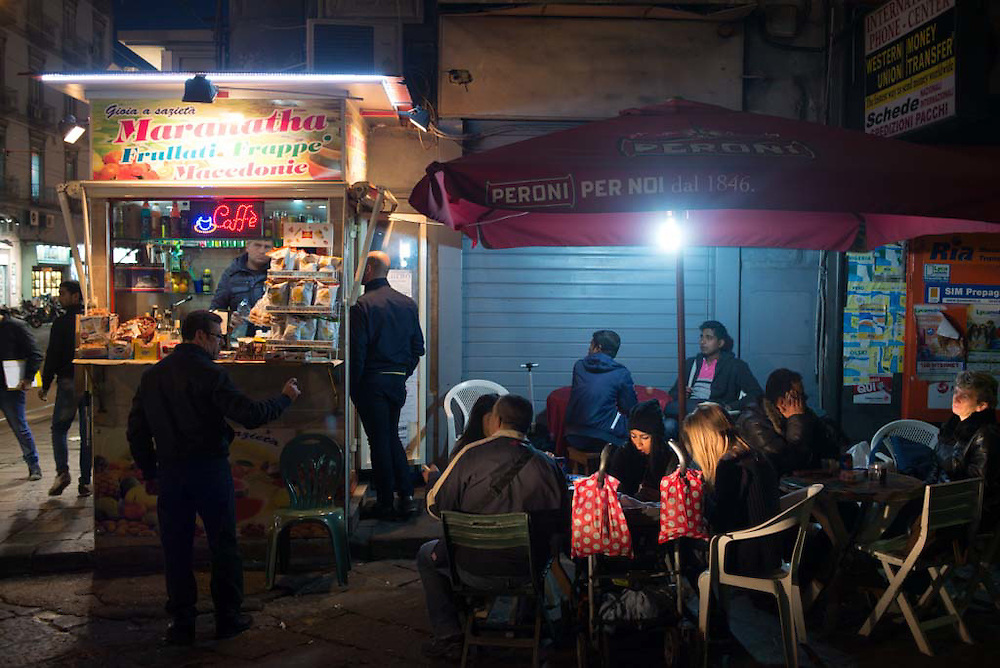 People eat at a roadside food stall in the city of Naples, Italy