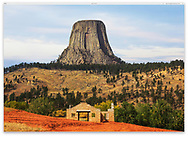 Devils Tower sits like a top hat above an abandoned stone building at the entrance to the park, Devils Tower National Monument, Wyoming, USA