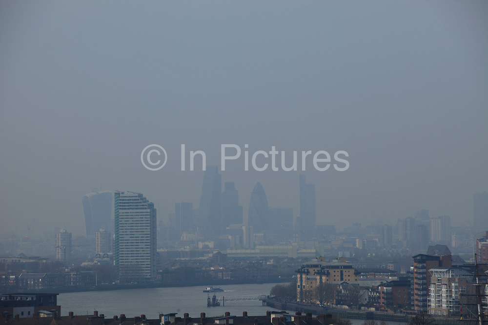London, UK. Wednesday 2nd April 2014. Industrial pollution from Europe and dust from the Sahara region creates a layer of smog over the City of London. Barely visible through the poplluted air, the buildings seem to disappear into the poor air quality. View from Greenwich Park towards the city skyline.