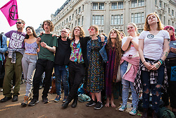 London, UK. 17th April 2019. Climate change activists from Extinction Rebellion, who continue to occupy Oxford Circus as part of International Rebellion activities, listen to the Declaration of Rebellion on the third day of International Rebellion activities.