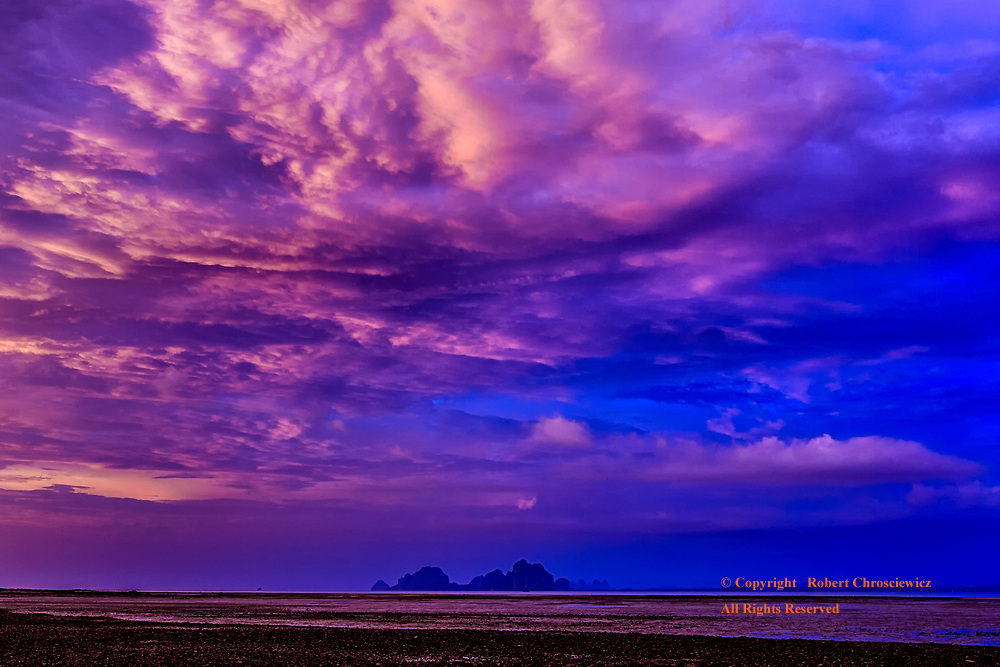 Clash of Colour: A jagged outline of clouds forms a temporary front between the pink, yellow clouds of the evening and the cool purple and blue of the night, over Ko Muk Thailand.