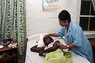 Patient caregiver Lucille Hutson, checks in on Felicia who is not feeling well at the St. Vincent De Paul Hospice center in Guyana. The center is a 20-bed facility that helps nurse HIV positive patients back to health in Gerogetown. Proper nutrition, a healthy lifestyle, and habits for taking medication at the proper time are emphasized while patients stay at the center. Sara A. Fajardo/Catholic Relief Services