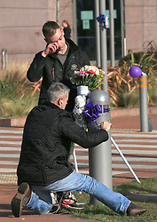 A man wipes his eyes as a colleague ties flowers to a post outside Alder Hey Children's Hospital in Liverpool, following the death of 23-month-old, Alfie Evans, who was being treated at the hospital.