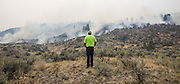 A resident of Omak watches wildfire creep down towards his neighbor's property off Vic Smith Road west of Conconully Road in central Washington Friday August 21, 2015. Neighbors and friends had been watching the property for the homeowner, who was away at work.<br /> <br /> Bettina Hansen / The Seattle Times