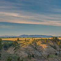 The sun rises over dry land wheat fields and coulees of the Upper Missouri River Breaks in central Montana.  In the background are the Judith, North Moccasin and Big Snowy Mountains.