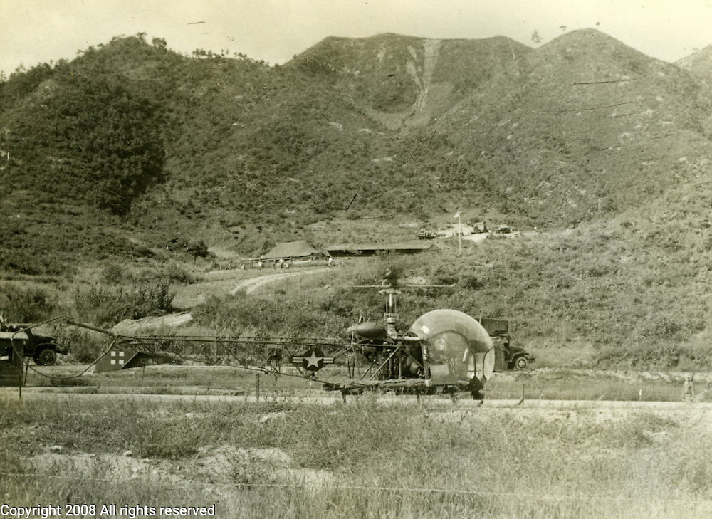"""A black and white photograph taken during the Korean War shows an OH-13 Sioux helicopter. The photo is marked, """"evacuation by helicopter. land mine casualty 1952 - flight to Chunchon."""""""