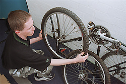 Resident of homeless hostel for people with learning difficulties replacing bicycle tyre,