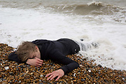 A young teenage drama student actor lies in the surf, playing the role of a character who has drowned in the sea, on location at the south coast, on 30th April 2017, at Winchelsea, England.