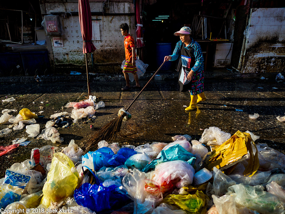 """04 DECEMBER 2018 - BANGKOK, THAILAND:  Workers clean up discarded single use plastic bags in Khlong Toei market. The issue of plastic waste became a public one in early June when a whale in Thai waters died after ingesting 18 pounds of plastic. In a recent report, Ocean Conservancy claimed that Thailand, China, Indonesia, the Philippines, and Vietnam were responsible for as much as 60 percent of the plastic waste in the world's oceans. Khlong Toey (also called Khlong Toei) Market is one of the largest """"wet markets"""" in Thailand. December 4 was supposed to be a plastic free day in Bangkok but many market venders continued to use plastic.   PHOTO BY JACK KURTZ"""
