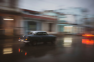 Panning shot of an old car driving early on a rainy evening on or very near Calzada de Infanta in Havana, Cuba. (December 2, 2014)