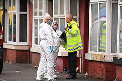 Forensics speak with a police officer at the scene in Claremont Road, Moss Side, Manchester, where ten people, including two children were taken to hospital after reports of gunshots at a street party.