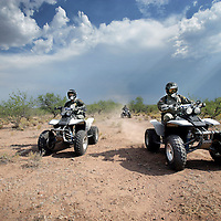 Verenigde Staten.Arizona.Nogales.juli 2005.<br /> Grenspolitie van Arizona verkent de grens tussen de VS en Mexico in de buurt van grensstad Nogales op hun vierwielige motoren (quads)  op zoek naar illegale vluchtelingen die vanuit Mexico de grens oversteken.Border Patrol. Woestijn. Vluchtelingen.Jagen. Droogte.Hitte.helm. Politietaken.Controle.<br /> Chase by police on illegal Mexicans who cross the border in Arizona.