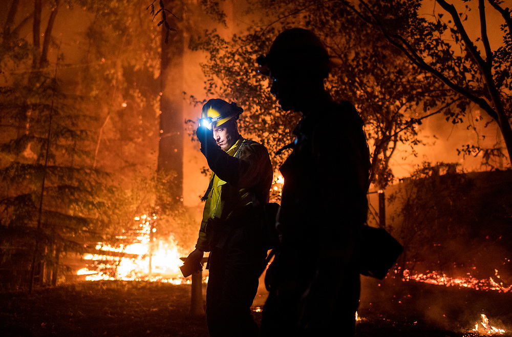 Firefighters walk by a house near Highway 236 as the CZU Lightning Complex fire rages near Boulder Creek, Calif. on Aug. 20, 2020.