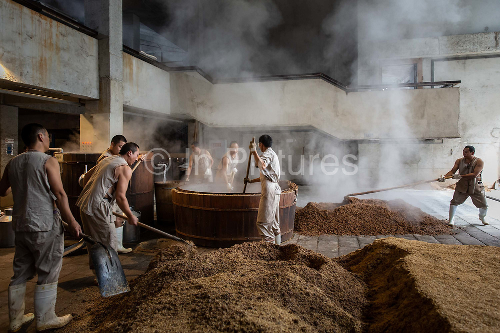 Workers use pitchforks and shovels to stir fermented grain ahead of alcohol extraction at a baijiu production facility that is part of the Shuijingfang museum, operated by Sichuan Swellfun Co., a unit of Diageo Plc in Chengdu, China, on Tuesday, Sept. 20, 2016. With less than 1 percent of baijiu, or white liquor, consumed abroad, Chinese distillers want to transform the fiery Chinese grain liquor into the new tequila for Americans and Europeans.
