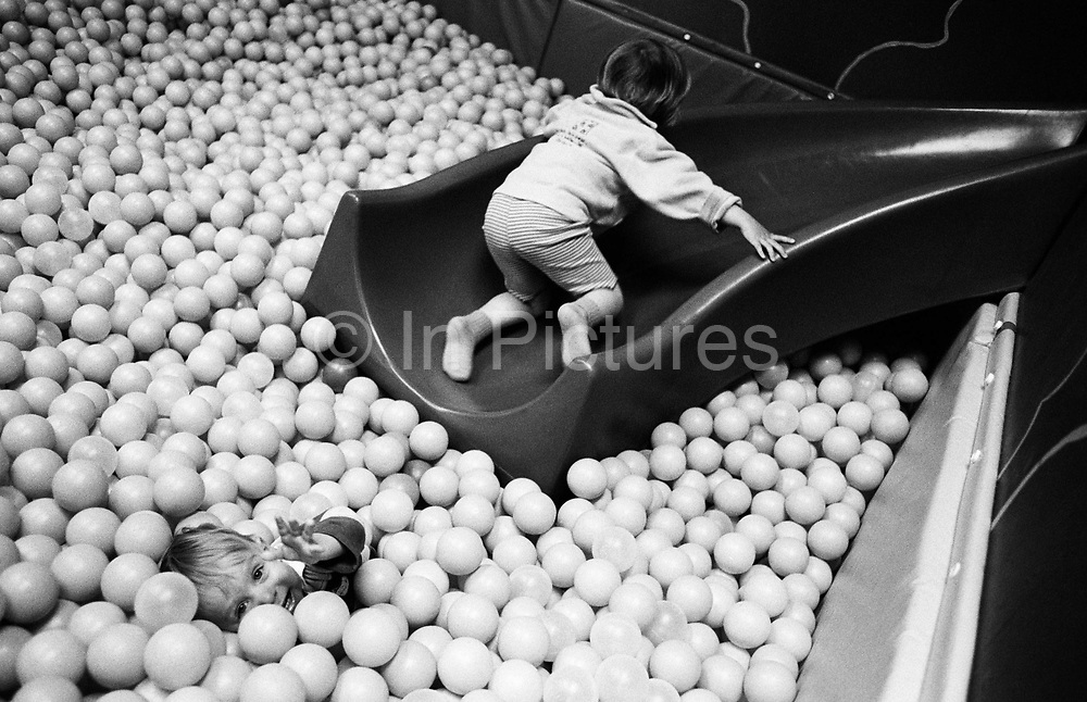 """While her brother apparently sinks beneath the surface of plastic balls, a three year-old girl scrabbles up a small slide in the Croydon branch of IKEAS's crèche facility, allowing parent shoppers to browse the store while their children frolic in the ball pond. Designed to encourage adventure and stimulate developing senses, the kids play on their own in this safe environment. From a personal documentary project entitled """"Next of Kin"""" about the photographer's two children's early years spent in parallel universes. Model released."""