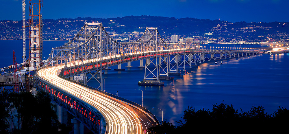 The former Eastern Span of the Oakland Bay Bridge is seen at dusk from Yerba Buena Island. The current Eastern Span can be seen under construction at right.