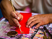 "04 FEBRUARY 2016 - BANGKOK, THAILAND:  A Chinese calligrapher writes out New Year greetings in Bangkok's Chinatown district, before the celebration of the Lunar New Year. Chinese New Year, also called Lunar New Year or Tet (in Vietnamese communities) starts Monday February 8. The coming year will be the ""Year of the Monkey."" Thailand has the largest overseas Chinese population in the world; about 14 percent of Thais are of Chinese ancestry and some Chinese holidays, especially Chinese New Year, are widely celebrated in Thailand.     PHOTO BY JACK KURTZ"