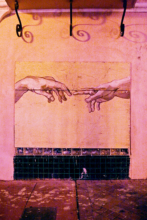 Wall painting on South Beach's Espanola Way copies famous Sistine Chapel detail by Michelangelo of God's hand giving life to Adam.