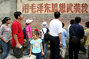 "People walk past a slogan advertising ""Mao Zedong thought. Today, Chuandixia is waking up. Middle-class Beijingers in their new cars make weekend trips to the Ming-era village, which lies 90 kilometers west of Beijing in the mountainous Mentougou District. Foreigners come to see examples of traditional Chinese culture. Artists come to paint, write, and even make movies."