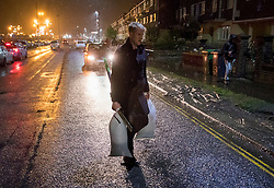 © Licensed to London News Pictures. 13/01/2017. Great Yarmouth, UK. A resident carries sandbags to his house under threat of flooding in Great Yarmouth. The Environment Agency has warned residents to prepare for evacuation as as they fear flooding at tonight's high tide. Photo credit: Peter Macdiarmid/LNP