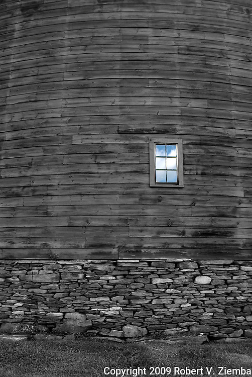 """""""Pakatakan Round Barn""""-A black and white image of a section of a round barn on a stone foundation with one window colored blue."""